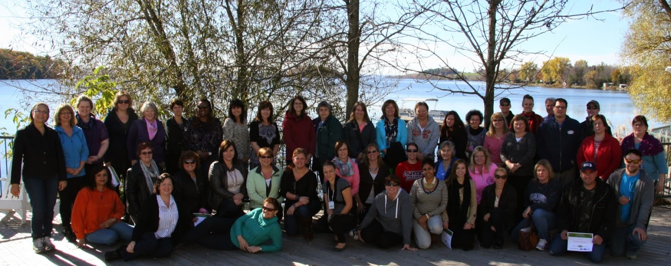 Group photo of conference attendees in front of trees and Rice Lake